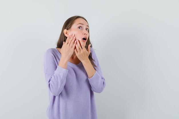 カジュアルなシャツの正面図で頬に彼女のにきびを絞る若い女性。
