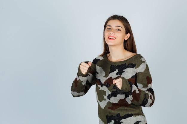 Девушка стоит в позе боя в свитере, юбке и выглядит весело