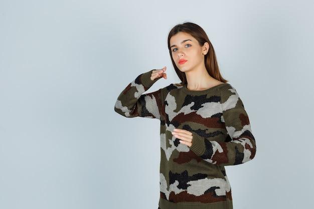 Молодая дама стоит в позе боя в свитере, юбке и выглядит уверенно