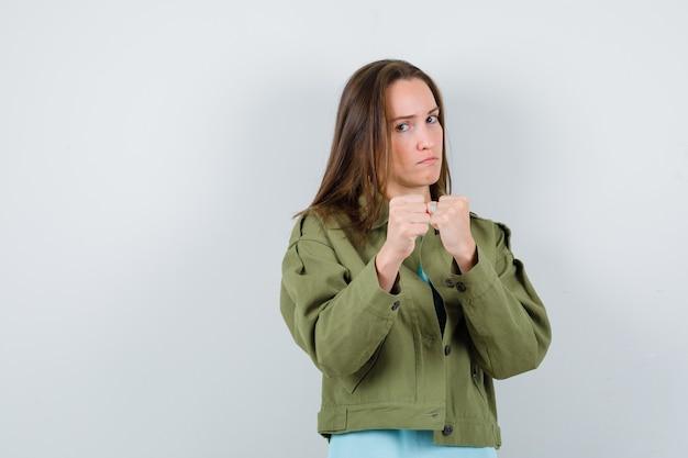 Молодая дама, стоящая в бою, позирует в футболке, куртке и выглядит уверенно, вид спереди.