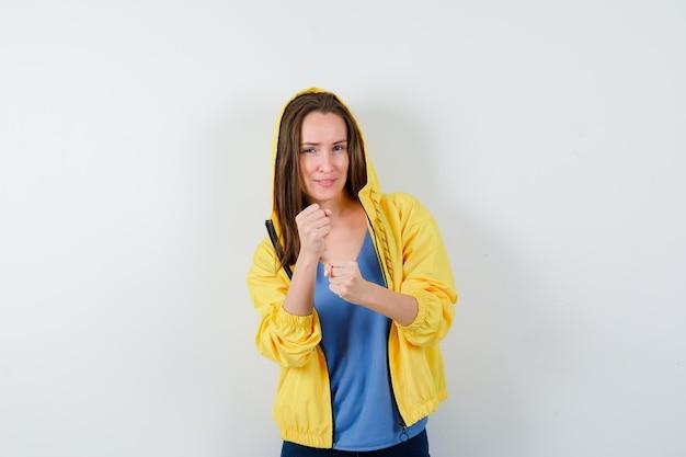 Tシャツ、ジャケット、自信を持って戦いのポーズで立っている若い女性