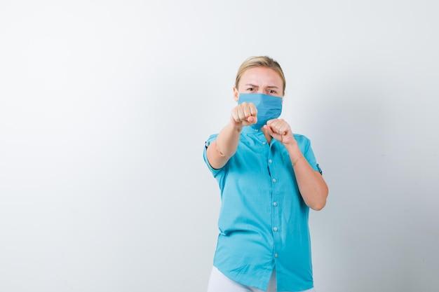Tシャツ、マスク、真剣に見える戦いのポーズで立っている若い女性