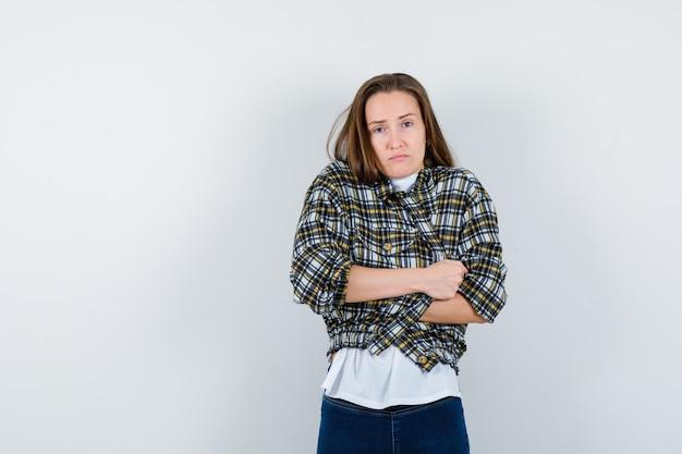 Tシャツ、ジャケット、ジーンズで怖いポーズで立って、物欲しそうに見える若い女性。正面図。