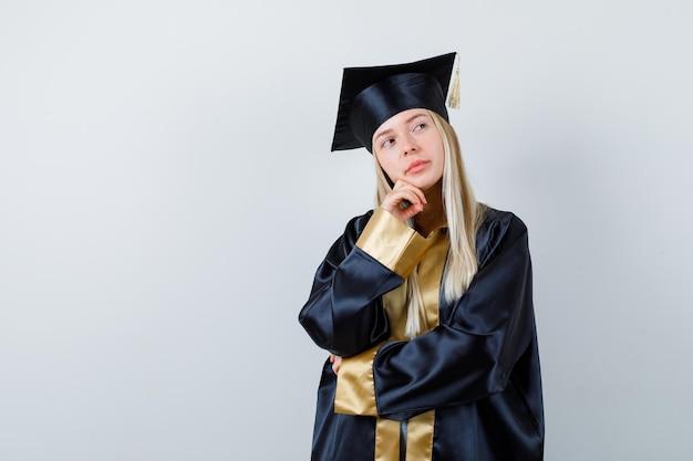 Молодая дама стоит в позе мышления в академической одежде и задумчиво