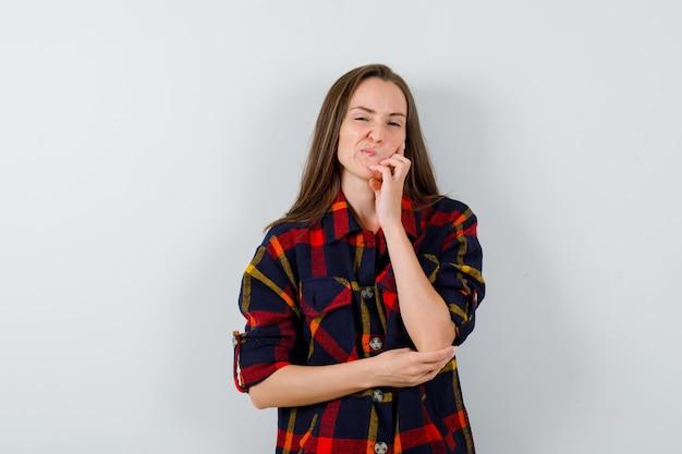 Молодая леди, стоящая в позе мышления в повседневной рубашке и выглядящая сомнительно, вид спереди.