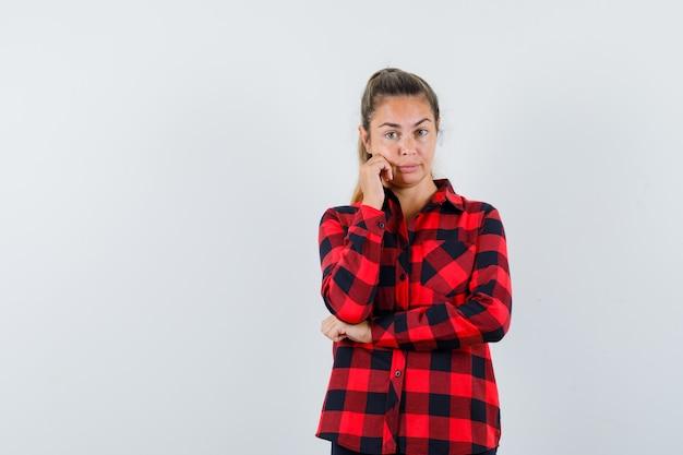 Молодая леди, стоящая в позе мышления в клетчатой рубашке и выглядящая заманчиво