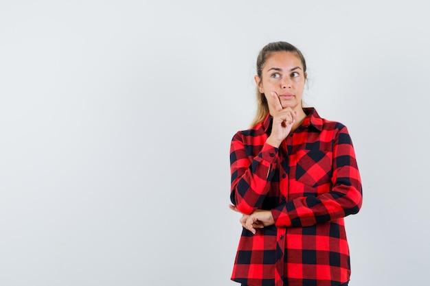 Молодая дама стоит в позе мышления в клетчатой рубашке и выглядит разумно