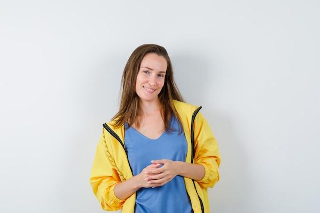 Tシャツでポーズを考えて立っている若い女性と自信を持って、正面図。