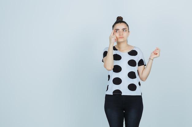 T- 셔츠, 청바지에 생각 포즈에 서 있고 사려 깊은, 전면보기를 찾고 젊은 아가씨.