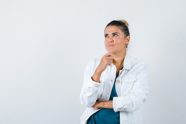 Молодая леди, стоящая в позе мышления в белой куртке и мечтательная, вид спереди.