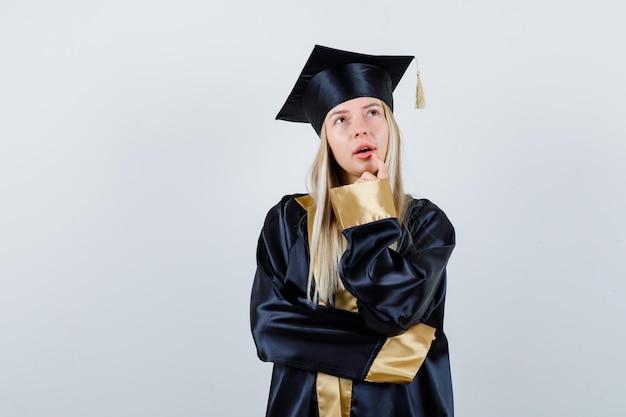Giovane donna in piedi in posa di pensiero in abito accademico e guardando pensierosa
