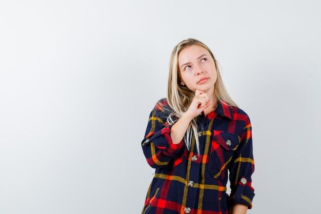 Giovane donna in piedi nel pensiero posa in camicia a quadri e guardando esitante, vista frontale.