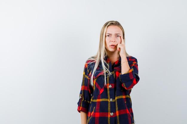 Giovane donna in piedi nel pensiero posa in camicia a quadri e guardando pensieroso, vista frontale.