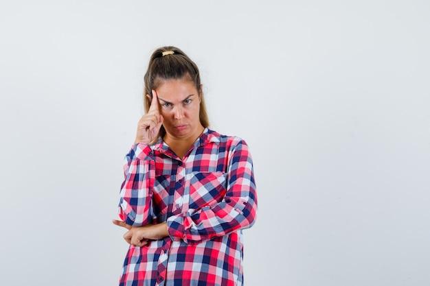 Giovane donna in piedi nel pensiero posa in camicia a quadri e guardando serio, vista frontale.
