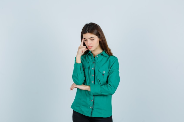 Young lady standing in thinking pose in green shirt and looking troubled. front view.