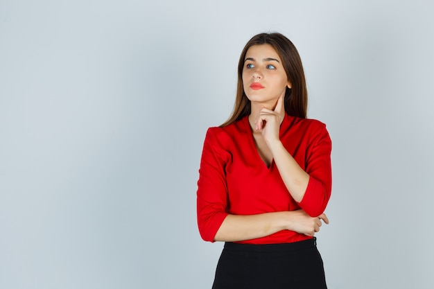 Young lady standing in thinking pose in red blouse, skirt and looking pensive