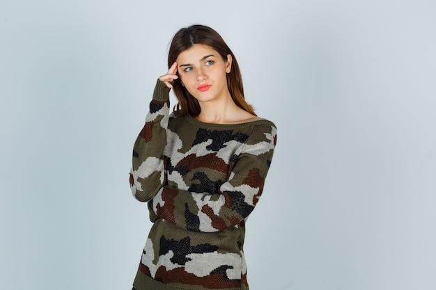 Giovane donna in piedi nella posa di pensiero in maglione, gonna e guardando pensieroso