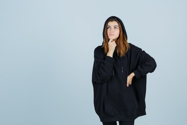 Giovane donna in piedi nella posa pensante mantenendo la mano sulla vita in felpa con cappuccio oversize, pantaloni e guardando pensierosa. vista frontale.