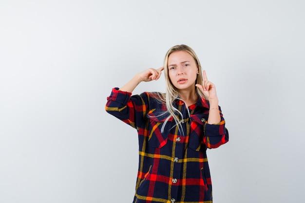 Giovane donna in piedi nella posa di pensiero mentre punta verso l'alto in camicia a quadri e sembra esitante, vista frontale.