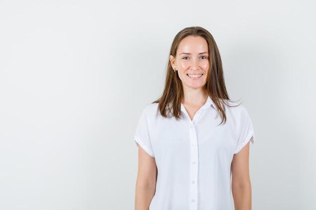 Молодая дама, улыбаясь в белой блузке и глядя оптимистично.