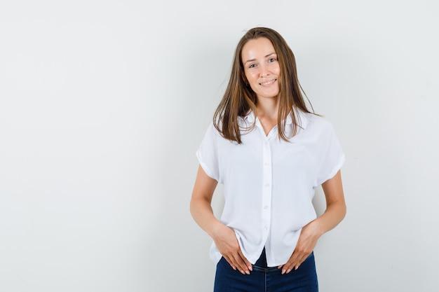 Молодая леди, улыбаясь в белой блузке