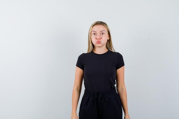 Giovane donna in piedi con le guance soffiate in maglietta, pantaloni e che sembra allegra. vista frontale.