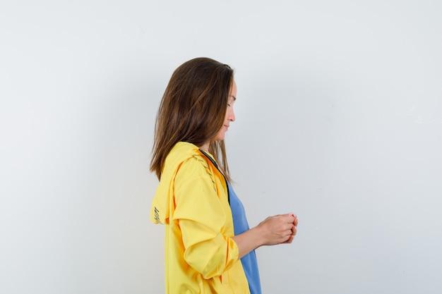 Giovane donna in piedi con le mani giunte in t-shirt, giacca e guardando pensieroso.