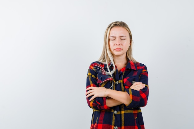 Young lady standing with crossed arms in checked shirt and looking wistful. front view.