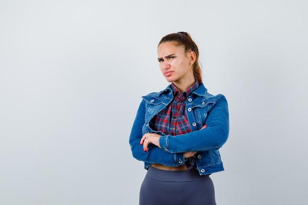 Giovane donna in piedi con le braccia incrociate in camicia a scacchi, giacca di jeans e guardando insoddisfatto, vista frontale.