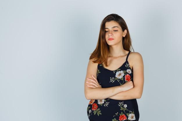 Giovane donna in piedi con le braccia incrociate nella parte superiore floreale e che sembra offesa