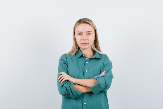 Giovane donna in piedi con le braccia incrociate in camicia verde e guardando fiducioso.