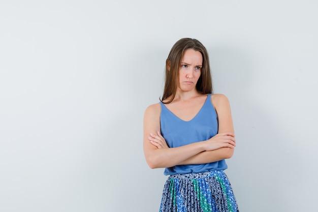 Девушка стоит со скрещенными руками в блузке, юбке и обиженно, вид спереди.