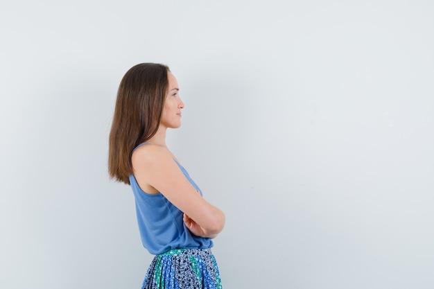 Девушка стоя со скрещенными руками в блузке, юбке.