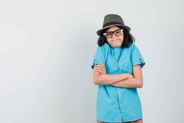 青いシャツ、帽子、眼鏡で腕を組んで立って、無知に見える若い女性