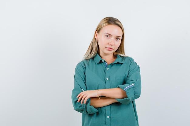 녹색 셔츠에 교차 팔으로 서 자신감을 찾고 젊은 아가씨.
