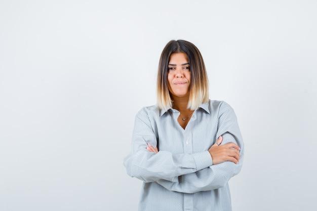 특대 셔츠에 팔짱을 끼고 서 있고 자신감이 넘치는 앞모습을 바라보는 젊은 여성.