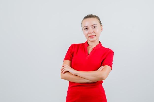赤いtシャツを着て腕を組んで立っていると陽気に見える若い女性