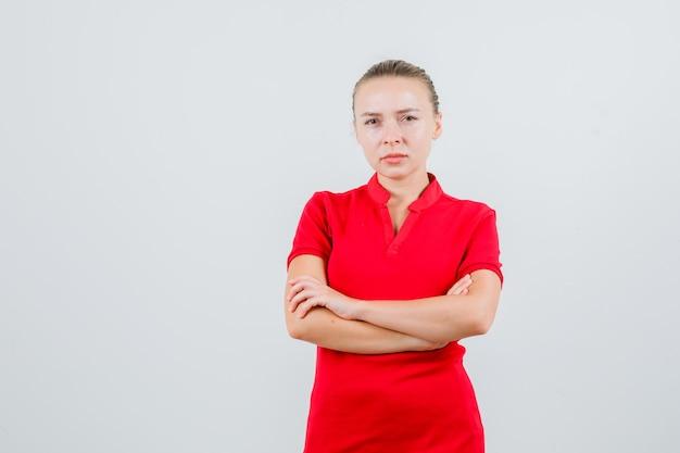 赤いtシャツで腕を組んで立っていると厳格に見える若い女性
