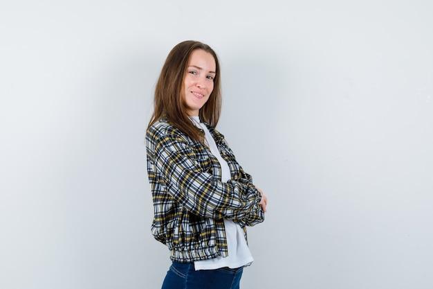 Молодая дама стоит со скрещенными руками в футболке, куртке и выглядит уверенно. передний план.