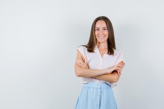 Tシャツ、スカート、陽気に見える腕を組んで立っている若い女性。正面図。