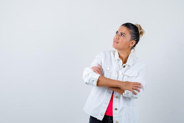 Tシャツ、白いジャケットで腕を組んで立って、注意深く見ている若い女性。正面図。