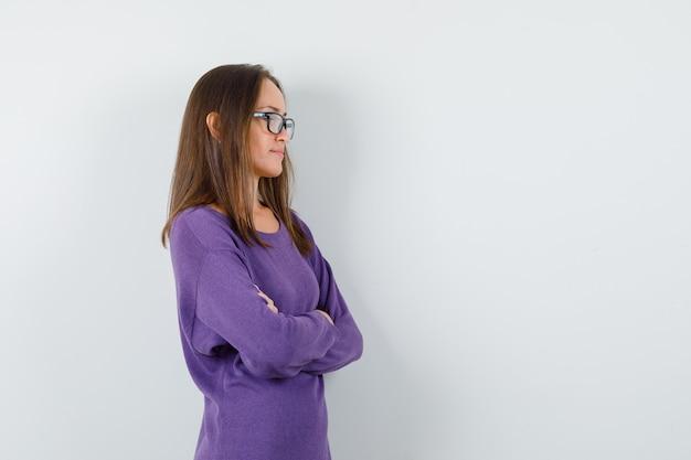 紫のシャツを着て腕を組んで立っていて、物思いにふける若い女性。 。