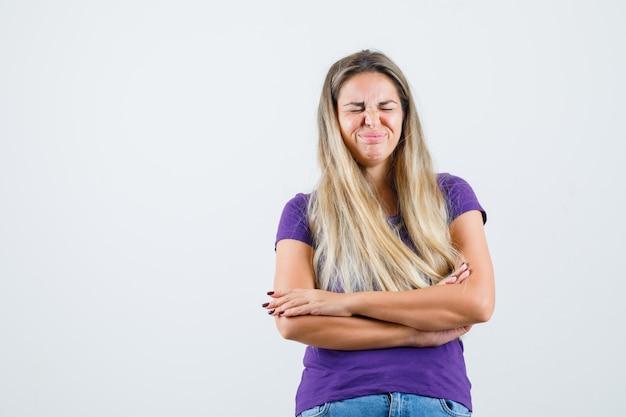 Молодая дама стоит со скрещенными руками в фиолетовой футболке, джинсах и выглядит счастливой. передний план. Бесплатные Фотографии