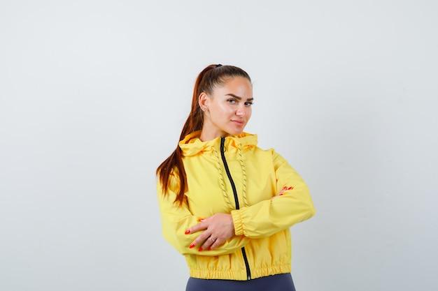 黄色のジャケットで腕を組んで立っていると自信を持って、正面図を探している若い女性。