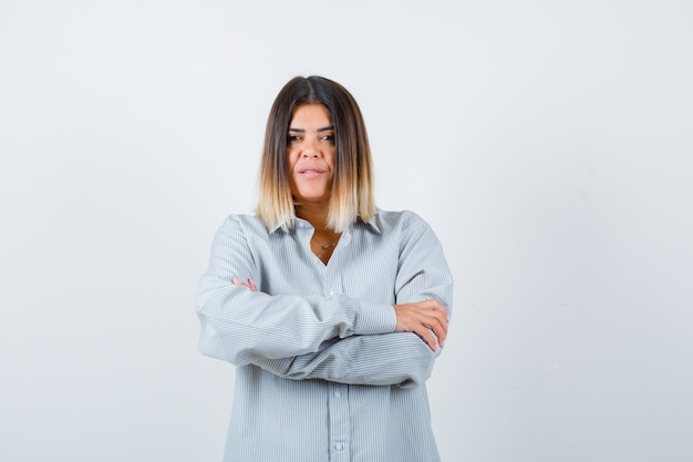 Young lady standing with crossed arms in oversized shirt and looking confident , front view.