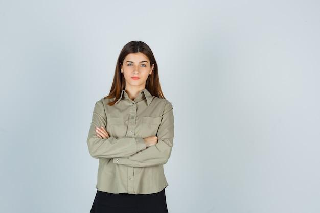Giovane donna in piedi con le braccia incrociate in camicia, gonna e guardando fiducioso