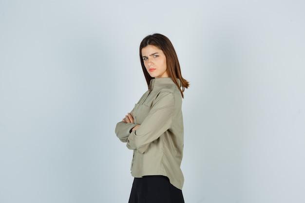Giovane donna in piedi con le braccia incrociate in camicia, gonna e sguardo dispettoso