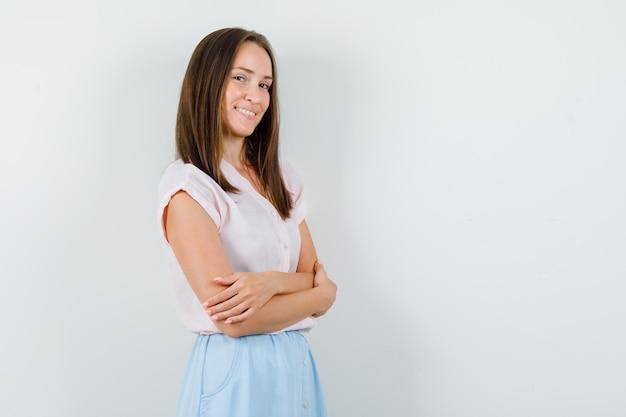 Giovane donna in piedi con le braccia incrociate in t-shirt, gonna e sembra allegra. vista frontale.