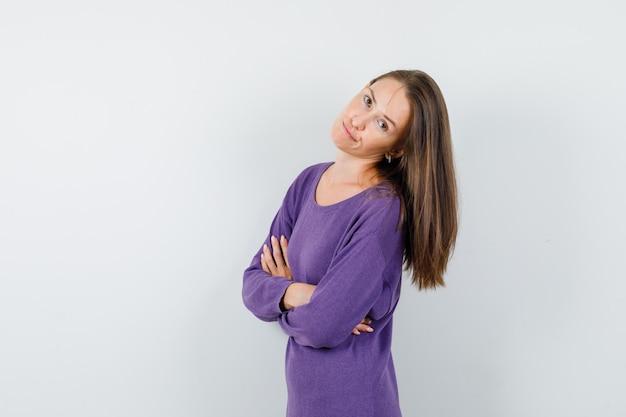 Giovane donna in piedi con le braccia incrociate in camicia viola e che sembra insoddisfatta. vista frontale.