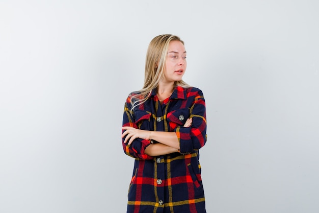 Young lady standing with crossed arms while looking away in checked shirt and looking confident. front view.